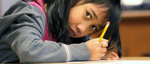 Girl writing with a pencil